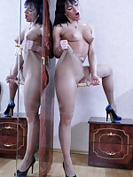 Busty brunette encased in fine patterned tights dildo toying by the mirror